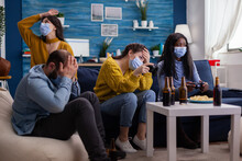 People Loosing Video Game Playing At New Normal Party During Social Pandemic With Face Mask, Keeping Distancing Against Spreading Covid 19 Virus Sitting On Couch In Living Room