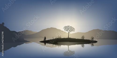 Fototapeta Concept du calme et de la tranquillité avec un homme qui pèche à la ligne, sur une petite île au milieu d'un étang, entouré de montagne