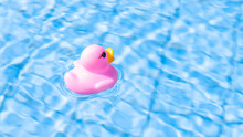 Duck Floating. Pink Rubber Toy For Kids Swim In Blue Water Of Summer Pool. Minimal Summer Concept.