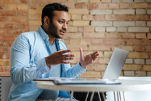 Middle Eastern Unshaven Man Gesturing While Working With Laptop