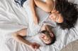 Leinwandbild Motiv top view of smiling multiethnic couple lying on bed