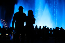 Silhouettes Of People At The Blue Fountain At Night.