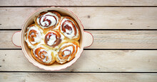 Freshly Made Cinnamon Buns In A Ceramic Dish Stand On A Plank Surface. Top View. Space For Text. Homemade Baking