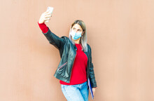 Happy Caucasian Woman Taking A Selfie After Lockdown Reopening On A Smooth Background Holding A Notebook. Young Girl Wearing Protective Face Mask Making A Self Portrait With A Smartphone. New Normal