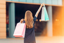 Back View, A Happy, Attractive Young Woman In Sunglasses, Shopping At The Mall, Shopping Bags In Hand. Shopping, Fashion
