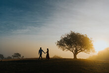 Silhouette Couple Walking On Land Against Sky During Sunset