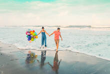 Big Surprise While On Trip. Walking With Balloons Along The Beach. Portrait Of Happy Couple.