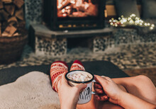 Personal Perspective Of Woman Relaxing On Sofa By Fireplace. Holding Cocoa.