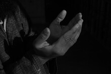 Midsection Of Man Praying Against Black Background