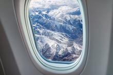 Airplane Window View At Snowy Mountains