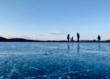 People On Frozen Lake Against Blue Sky During Winter