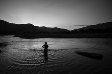 Silhouette Man Standing In Lake Against Sky