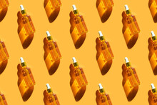 Seamless Pattern Of Serum In Glass Bottle On Orange Background. Beauty, Cosmetology, Dermatology Concept. Top View, Flat Lay.