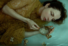 The Mermaid - Selfportrait - Woman With A Lace Dress Lying In Water With A Magnifier In Her Hands