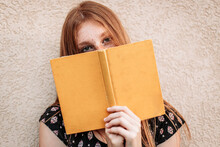 Teen Ginger Student Girl Holding A Book, Face Hidden With A Book