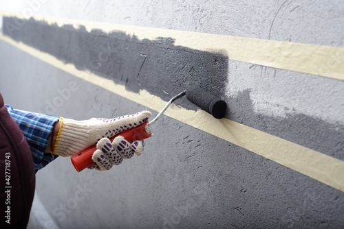 female painting a wall with masking tape and roller - fototapety na wymiar