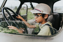 Boy Driving While Sitting In Car