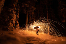 Man With Wire Wool On Snow Covered Landscape At Night