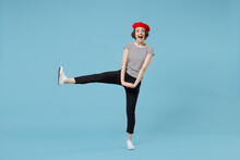 Full Length Of Young Smiling Trendy Woman With Short Hairdo In French Beret Red Hat Striped T-shirt Stand With Outstretched Leg Intertwined Fingers Isolated On Pastel Blue Background Studio Portrait.