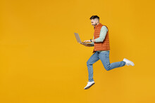 Full Length Side View Young Strong Powerful Fun Caucasian Man 20s Years Old In Orange Vest Mint Sweatshirt Jump High Hold Laptop Pc Computer Chat Online Isolated On Yellow Background Studio Portrait.