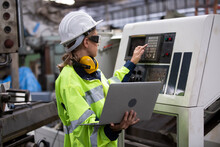 Engineer Using Laptop While Operating Machine In Factory