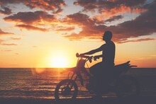 Silhouette Man Riding Bicycle On Beach Against Sky During Sunset