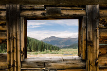 Scenic View Of Landscape Against Sky From A Wooden Cabin Window