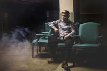 Young Man Sitting On Chair In A Smoky Basement