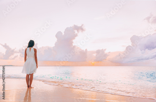 Paradise beach elegant woman walking relaxing watching pink sunset on idyllic travel Caribbean vacation destination. Clouds and ocean serene scenery relaxation.