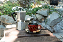 Outdoor Summer Breakfast With Cup Of Coffee Made With Geyser Coffeemaker And Cookie Stand On Old Wooden Table In Summer Garden. Leisure And Recreational Concept
