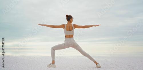 Obraz Rear view athletic woman doing yoga, body stretch outdoors on salt coast lake - fototapety do salonu