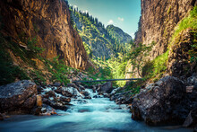Scenic View Of Stream Flowing Through Rocks In Mountains