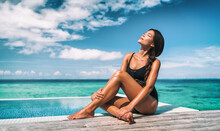 Swimsuit Model Beauty Skincare Suntan Asian Woman Posing Sunbathing Tanning In Black One Piece Bathing Suit. Beautiful Girl Relaxing At Overwater Infinity Pool Luxury Resort. Spa, Wellness, Laser.