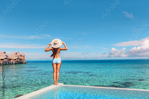 Luxury vacation hotel in Tahiti woman relaxing at infinity pool looking over ocean in French Polynesia travel summer holiday.