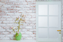 Magnolia Branch In A Green Vase With White Brick Wall In The Background. Copy Space. Spring Flowers In The House. Magnolia Flowers In The House.