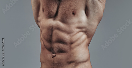 Bodybuilder with sexy muscular athletic body with bare torso and strong belly with six packs or abs in studio on grey background Fototapeta