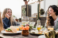 Happy Friends Eating Vegan Food With Wine Outdoors In Summer Sunset At Patio Restaurant - Main Focus Right Woman Face