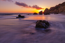 Waves Wash Over A Rock As The Sun Sets In Malibu
