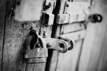 A Rusty Old Lock On A Wooden Door.