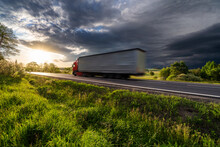 Motion Blurred Red Truck Driving On The Asphalt Road In Rural Landscape At Sunset With Dark Storm Cloud