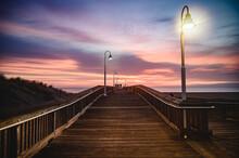 Fishing Pier Over Sea Against Sky During Sunrise