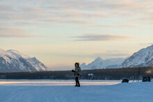 Woman Holding A Tripod And Camera Walking Along A Frozen Lake In Northern Canada On A Cold, Sunset Afternoon In Spring Time April. Wearing Beige Jacket And Black Pants.