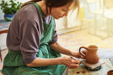Woman Master Potter Sculpts A Jug Of Red Clay In The Workshop