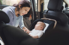 Happy Smiling Beautiful Asian Young Mother Putting Her Baby Son Into Car Seat And Fasten Seat Belts In The Car
