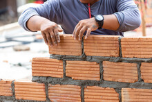 A Close Up Of Orange Bricks With The Hands Of A Mason We Are Building The Walls Of The House, Designing The Arrangement Of Bricks To Create The Walls