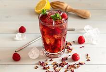 Hibiscus Ice Tea Or Karkade Lemonade With Raspberries, Mint, And Lemon On A Wooden Table.