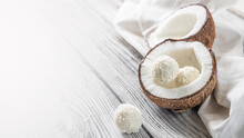 Two Halves Of Coconut And Coconut Sweets On A Wooden Table .  Coconuts On A White Napkin . Handmade Coconut Sweets With A Copy Space  .  Horizontal Orientation Picture With A Coconut .