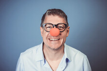 Business Man With Blue Shirt And Black Glasses And Red Clown Nose Posing In Front Of Blue Background In The Studio