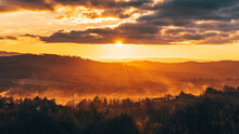 Eerie Scenery Of A Golden Mountain Horizon At Cloudy Sunset