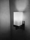 Square lamp with light beam on wall near bed in budget hotel in black and white concept